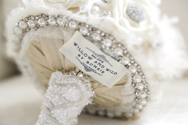 "Close up of ""Willow and Wild"" tag at the back of an ornate hand made fabric bouquet"