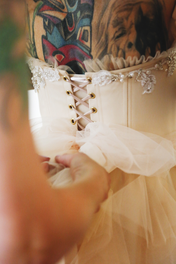 A bow being tied at the back of a wedding dress