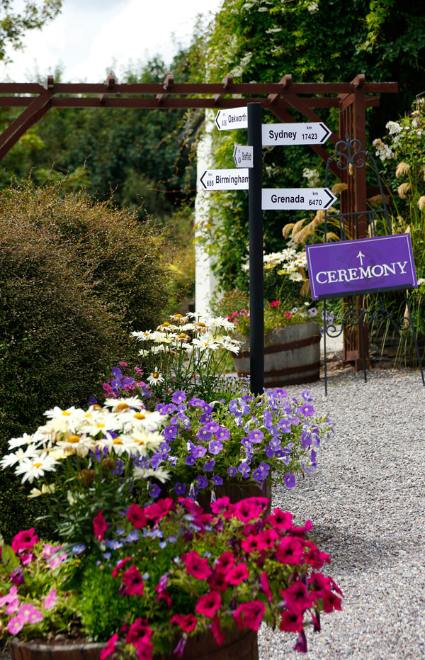 A signpost surrounded by colourful flowers at a wedding at Barnabrow