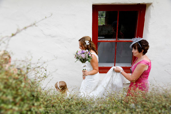 A bride walks by an old sash window at Barnabrow on the way to her wedding her mum holds the back of her dress