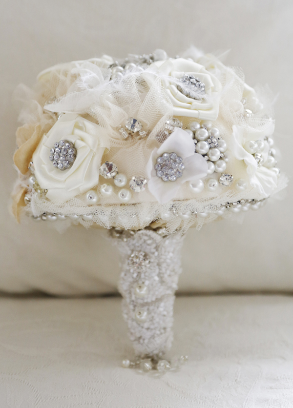 A bridal bouquet made of fabric flowers and encrusted with pearls and diamonds