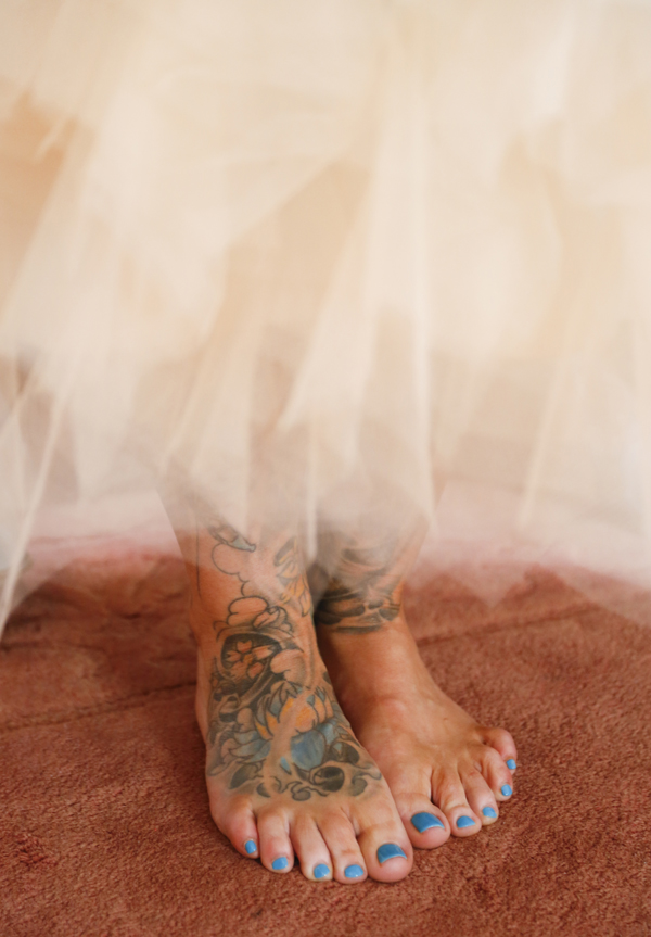 Brides feet, with tattoos and blue toenails