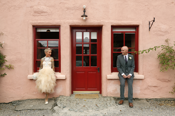 Bride and groom sit on windowsills of a pink and red cottage