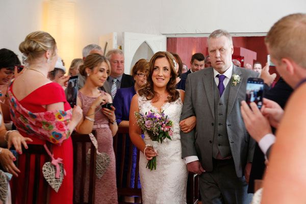 smiling bride is walked down the isle by her dad