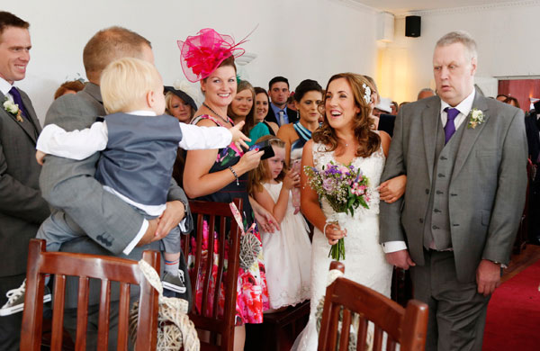 Bride reaches the top of the isle and her son is excited to see her, his arms are stretched out towards her