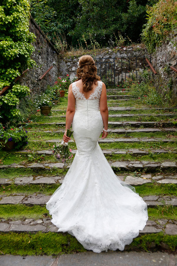 Colour photograph of the back of a brides wedding dress taken on the steps at Barnabrow